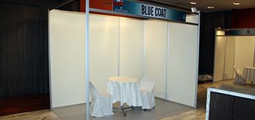 Stand esquina de 3x2m con cenefa impresa, cubre piso, iluminación, 1 mesa y 2 sillas.
